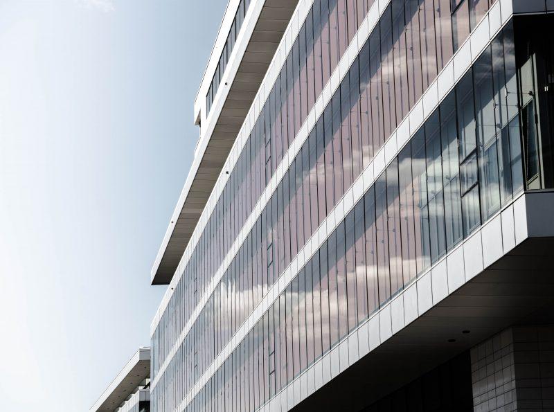 Byggnad med fönster som reflekterar blå himmel