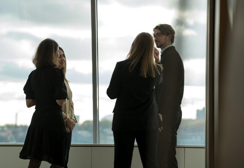 Flera medarbetare hos Mannheimer Swartling framför fönster